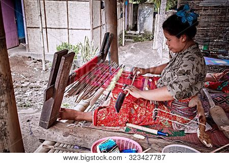 Bali, Indonesia - Sep 22, 2019: Weaver woman behind a loom, handmade manufacturing fabric and carpets. Handmade on a wooden loom manufacturer of thread, fabric and carpets.