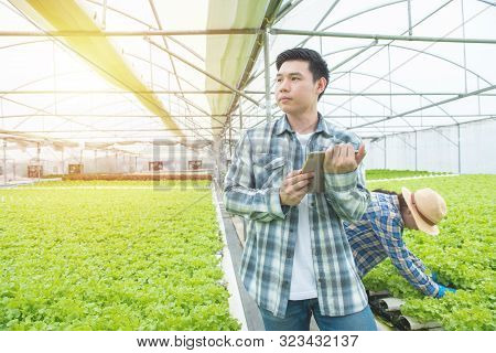 Portrait Of Young Asian Professional Farmer Man Hand Hold Tablet With Asian Woman Coworker Working I