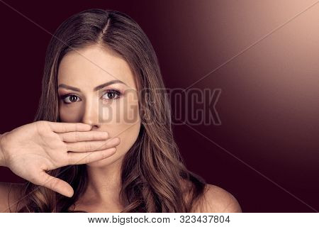 Young Brunette Covering Nose With Hand Because Of Bad Smell On Dark Red Color With Light Spot Backgr