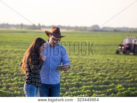 Farmers With Tablet In Front Of Tractor In Field