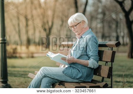 Prepossessing Elderly Madam In Glasses Reading Intently A Book