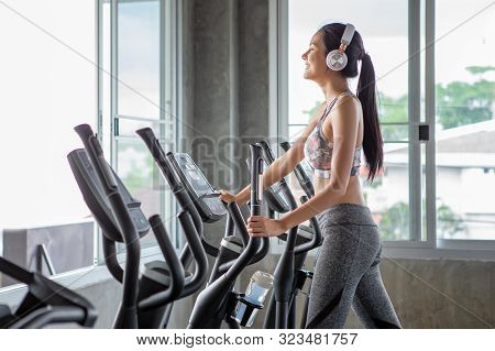 Beautiful Young Asian Woman Exercise On Elliptical Machine And Listening Music With Headphones Relax