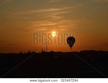 Hot Air Balloon Flying Over The City At Sunset, South Bohemia, Czech Republic