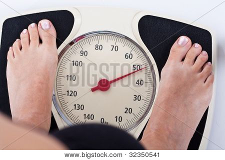 Woman measuring her weight on a balance