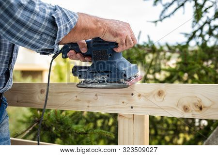 Adult carpenter craftsman with electric sander smoothes the boards of a wooden fence. Housework do it yourself. Stock photography. poster