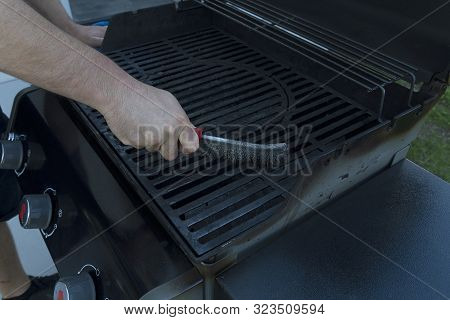 A Man Brushes An Street Black Grill With An Iron Brush. Grill Preparation For Frying Meat.