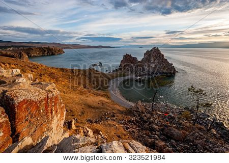 Beautiful View Of The Sacred Rock Of Shamanka On The Island Of Olkhon At Sunset. There Are Light Clo