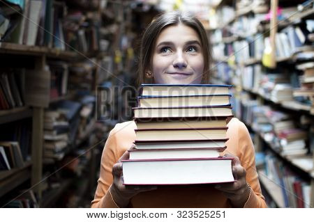 Young Girl Student Holds A Stack Of Books In The Library, She Searches For Literature And Offers To