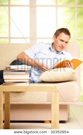 Man sitting on sofa in room and reading book, wearing casual clothes.