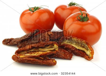 Some whole fresh tomatoes and sun dried tomato pieces on a white background