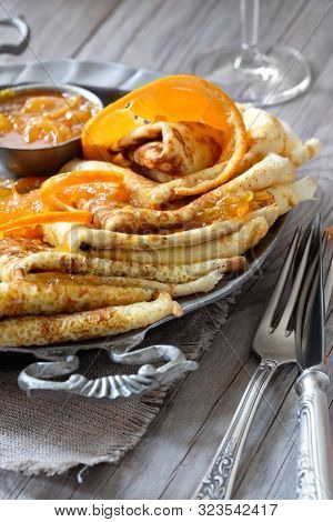 Crepes Suzette On Vintage Metal Plate On Wooden Table Served With Orange Sauce, Close-up On A Plate