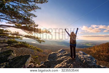 Female Hiker Raising Arms In Celebration To The Sun Setting Over A Magnificent Vista At The Top Of A