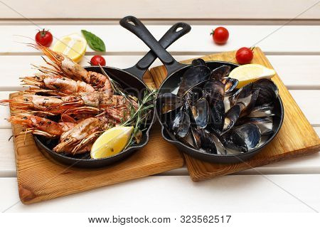 Prawns And Mussels In Pans On An Wooden Background