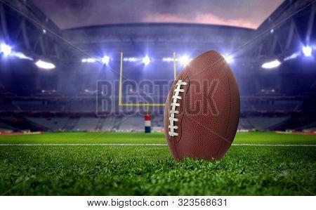 American Football Ball In Stadium At Night Under Spotlights
