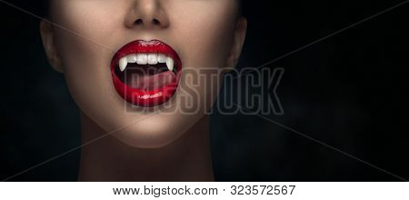 Sexy Vampire Woman's red bloody lips close-up. Vampire girl licking fangs with tongue. Fashion Glamour Halloween art design. Close up of female vampire mouth, teeth. Isolated on black background