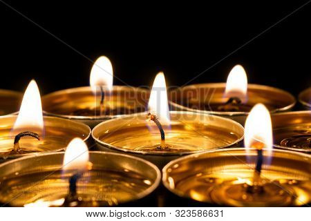 Golden Close-up Candles Burning In The Black Background. The Concept Of Mourn, Grief, Mourning Or Ch