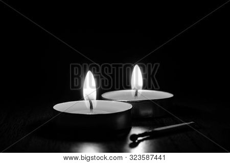 Close-up Candles Burning In The Black Background. The Concept Of Mourning, Grief Or Sorrow. Black An