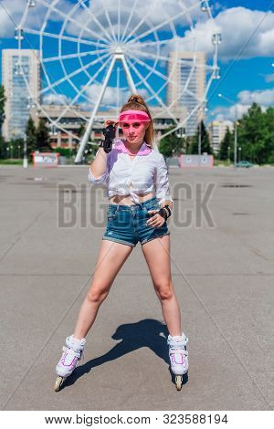 Portrait Of An Emotional Girl In A Pink Cap Visor And Protective Gloves For Rollerblades And Skatebo
