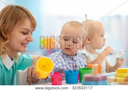 Cute Babies In Day Care. Group Of Kids Playing Toys With Kindergarten Teacher. Children Lesson In Cr