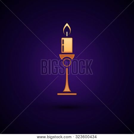 Gold Burning Candle In Candlestick Icon Isolated On Dark Blue Background. Old Fashioned Lit Candle.