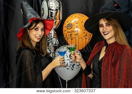 Two young adult and teenager girls celebrating a Halloween party carnival Festival in Halloween costumes drinking alcohol cocktail poster