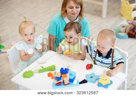 Worker With Group Of Babies In Creche. Top View Of Small Kids On Lesson In Kindergarten