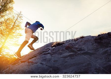 Man Runs Uphill By Big Rock Against Sunset Sky
