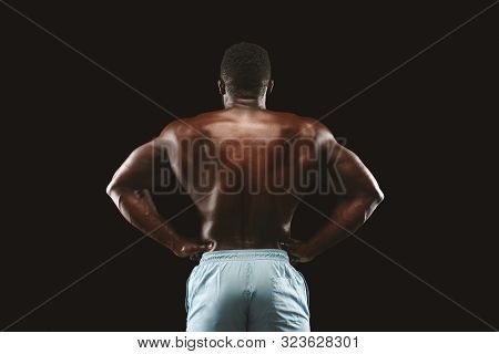 Unrecognizable African American Bodybuilder Showing Strong Athletic Trapezius, Black Background
