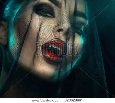 Vampire Halloween Woman portrait with black veil on a face. Beauty Sexy Vampire Girl with teeth, bloody red lips. Vampire makeup Fashion Art design. Mysterious model girl make up. Fangs. Darkness