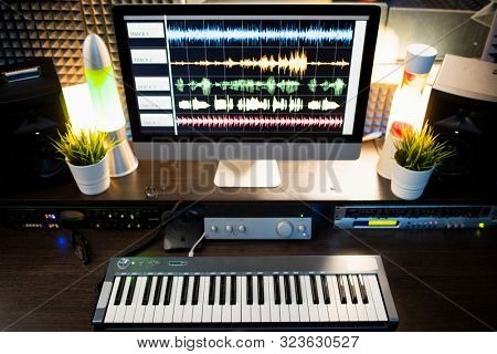 Piano keyboard and computer screen with waveform sound visualization on workplace of modern musician or deejay in studio