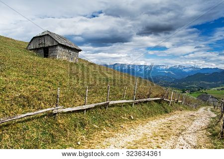 A Small And Old Building, A Wooden Shack, On A Hill Near The Mountains. A Path That Leads To The Mou