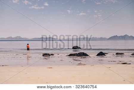 Tourist Woman Relaxing Walking On Sea Shore. Coast Of Gimsoya Island, Gimsoysand Sandy Beach In Summ