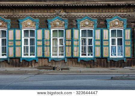 Window With The Wooden Carved Architrave In The Old Wooden House In The Old Russian Town. Irkutsk