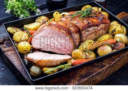 Traditional roasted dry aged veal tenderloin with carrots and potatoes offered as closeup on a metal tray