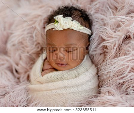 Sleeping African newborn baby girl with diadem
