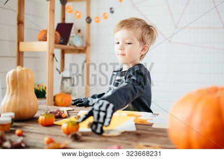 Halloween Party. Little Boy In A Skeleton Costume Is Ready To Celebrate Halloween. Boy In A Hallowee