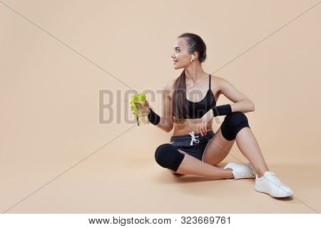 A Cute Athletic Brunette Girl, In A Tight-fitting Sports Uniform, Sits, Rests After A Workout, In Bl