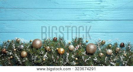 Fir Tree Branches With Christmas Decoration On Light Blue Wooden Background, Flat Lay. Space For Tex