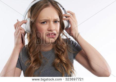 Displeased Teen Girl In Wireless Headphones Biting Bottom Lip
