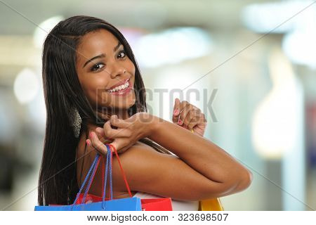Young african American girl with shopping bags inside a mall