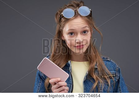 Annoyed Teen Girl With Brown Hair Holding Cellphone And Pursing Lips