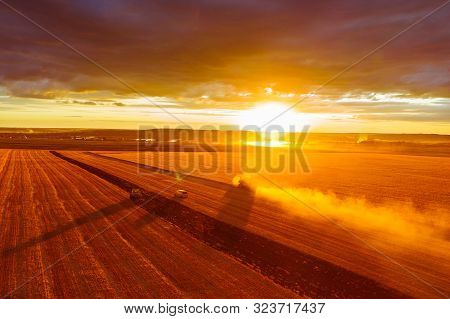 Combine Harvester Harvests Wheat In The Field At Sunset In Autumn In Russia. View From A Height Of E
