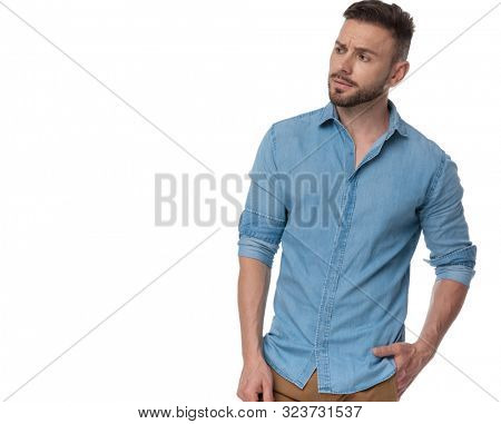 young casual man with blue shirt standing with one hand in pocket and looking to a side intrigued on white studio background
