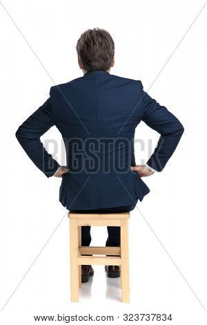 rear view of a formal business man with navy suit sitting with hands on his waist intrigued on white studio background