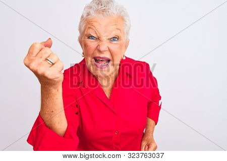Senior grey-haired woman wearing red casual shirt standing over isolated white background angry and mad raising fist frustrated and furious while shouting with anger. Rage and aggressive concept.