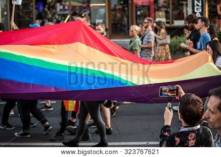 Belgrade, Serbia - September 15, 2019:  Woman Filming A Crowd Of Protestors Holding A Giant Rainbow