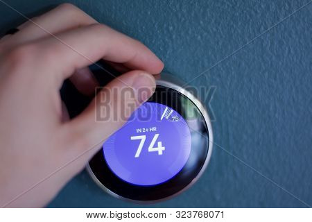 Smart Learning Thermostat On Blue Wall.
