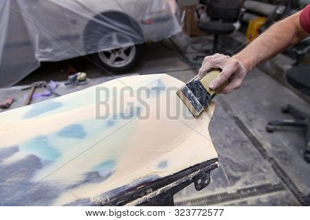 A Man Prepares A Car Body Element For Painting After An Accident With The Help Of Grinding Abrasive