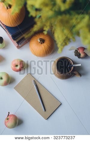 Autumn Still Life With Closed Notebook And Pencil, Books Stacked, Orange Pumpkins, Apple, Clay Drink