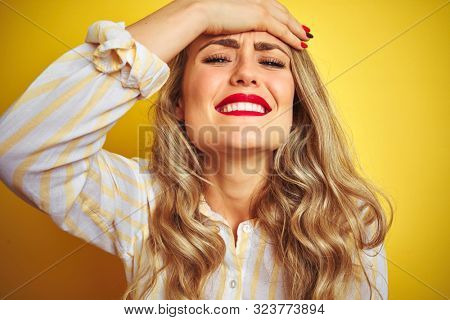 Young beautiful woman wearing stripes shirt standing over yellow isolated background stressed with hand on head, shocked with shame and surprise face, angry and frustrated. Fear and upset for mistake.